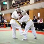 強烈な右下段廻し蹴りで相手の身体を折る小椎尾選手(左)